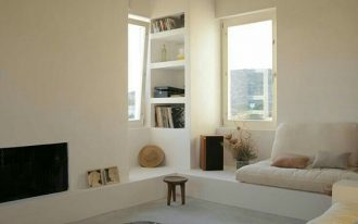 sunken livign room, grey floor rug, white wall, brown ceiling, off white sofa, wooden tables, TV, built in shelves, small nook