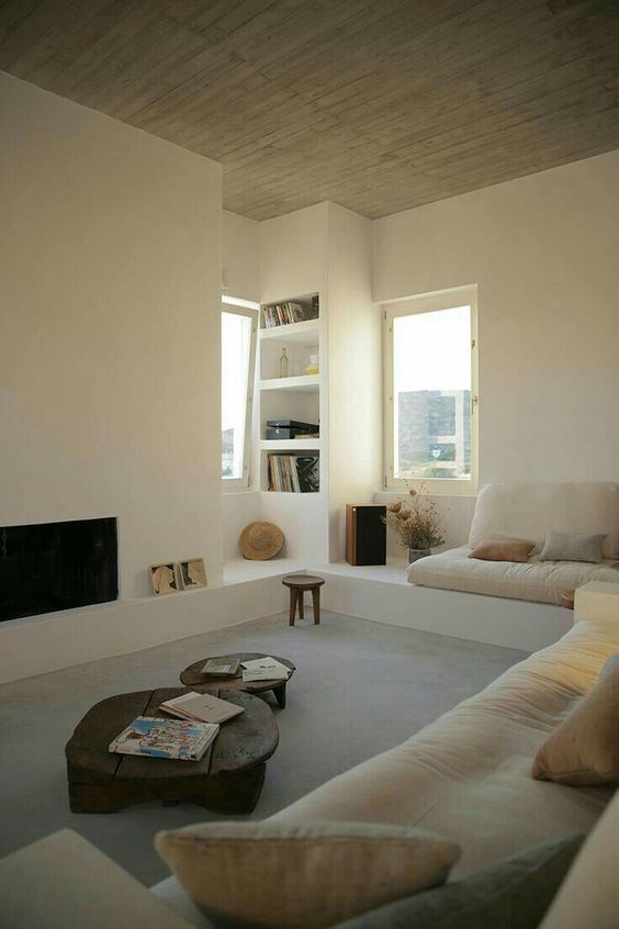 sunken livign room, grey floor rug, white wall, brown ceiling, off white sofa, wooden tables, TV, built in shelves, small nook