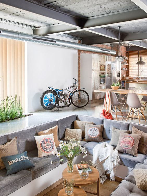 sunken living room, white seamless floor, wooden pit floor, white built in sofa, grey cushion, pillows, wooden round small coffee table, industrial ceiling