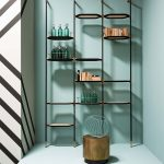 Wal Shelves With Black Rod, White Hexagonal Boards, Green Wall, Golden Stools