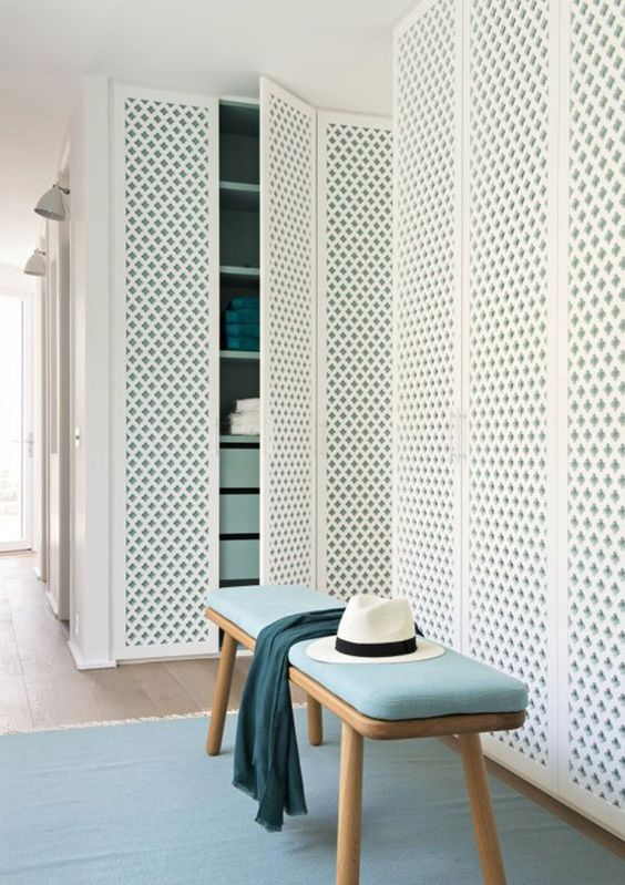 white grid doors on built in cupboard, blue rug, wooden bench with blue cushion