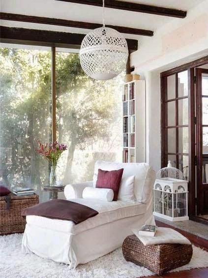 white lounge chair, wooden floor, white rug, large glass window, white bookshelves, wooden rattan chests, white pendant
