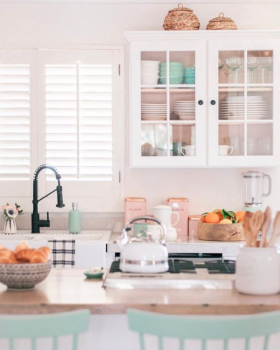 white pink wall, white upper cabinet, wooden top island, green wooden chair, white top kitchen, black faucet, window