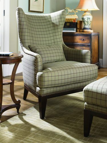 white plaid chair with black lines, ottoman, green rug, wooden side table, wooden cabinet