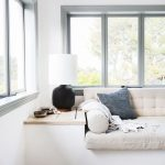 Window Nook With Built In Bench, Wooden Built In Side Table, White Cushion With Pillow And Back, Black Table Lamp, Wooden Floor, White Rug