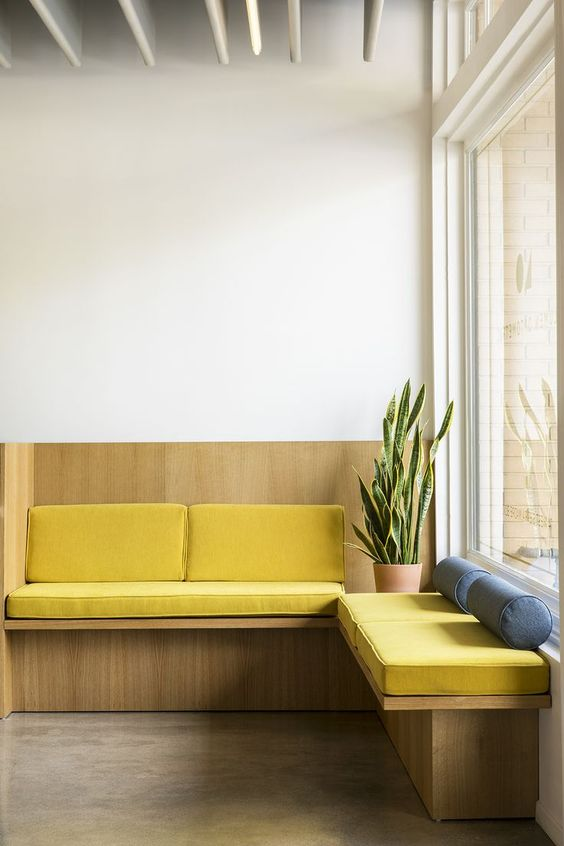 window seat in the corner, large window, yellow suchion, with shelves bottom