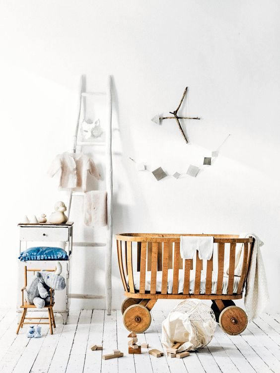 wooden baby crib with round wheel, white wooden floor, white wall, white wooden rack