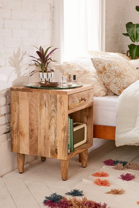 wooden bedside table, wooden floor, white open brick wall, bed with pillows