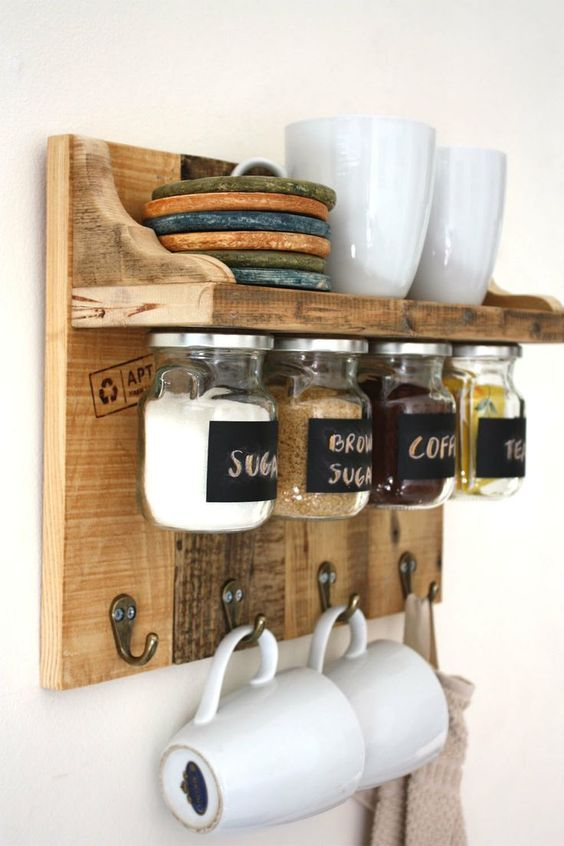 wooden floating shelves with seasoning bottles under, hooks for mugs