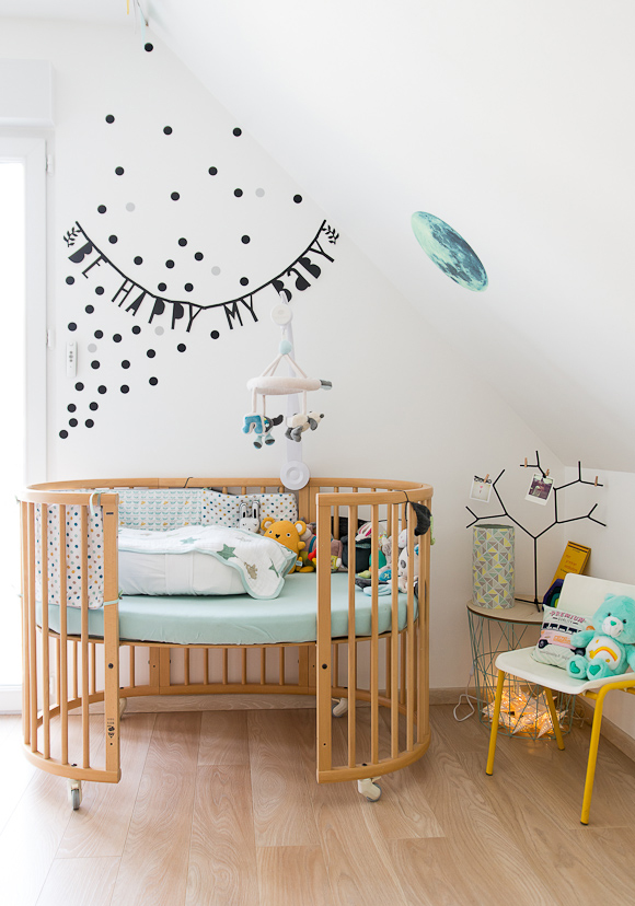 wooden round baby crib, green cushion, wooden floor, white sloping ceiling, little white chair