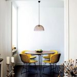 Yellow Cushion On Black Wired Chairs In The Dining Room, Dark Wooden Floor, White Wall, Round Wooden Table