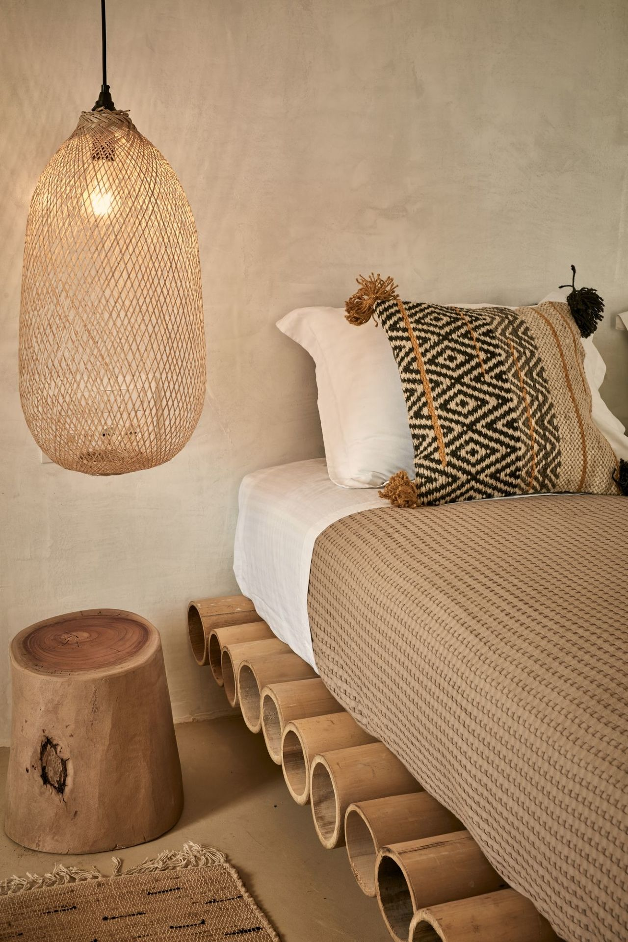 bamboo bed platform, brown floor, cream wall, rattan rug, rattan pendant
