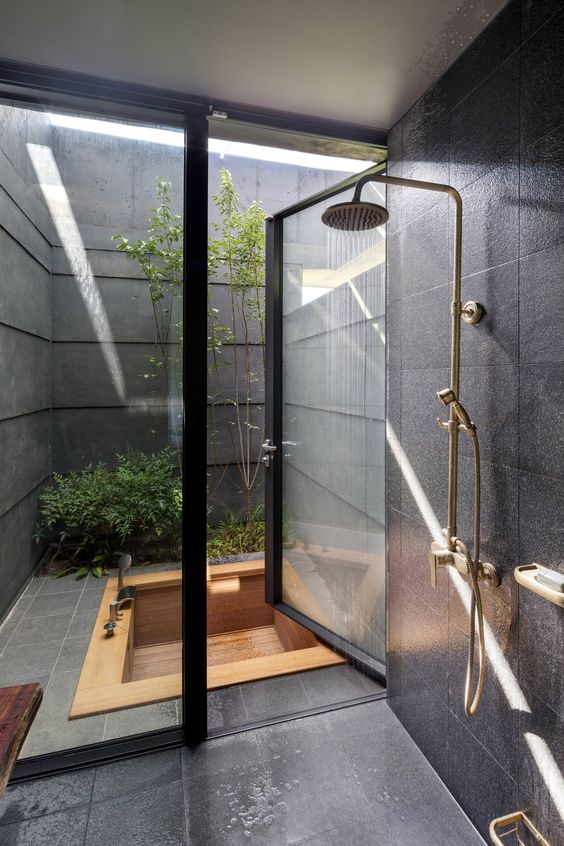 bathroom, black floor tiles, black wall tiles, wooden patterned sunken tub outside, golden shower, glass door