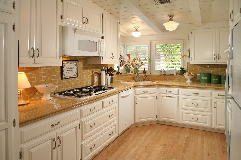corner kitchen sink cabinet wooden floor windows pendant lamp white oven white dishwasher stovetop brown countertop tiles brown backsplash white beams cans