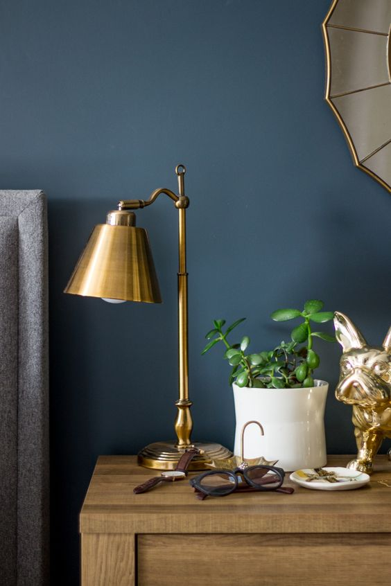 golden table lamp, wooden side table, blue wall
