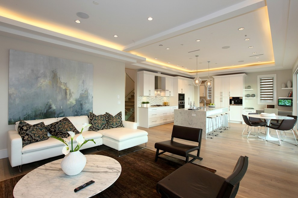 kitchen family room recessed lighting wallart white sectional sofa brown chairs brown rug white marble coffee table white marble island white cabinets stovetop white pedestal tab