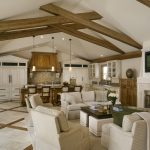 Kitchen Family Room Wooden Beams White Sofa Cream Chairs Coffee Table Fireplace Wooden Cabinets Wooden Island Pendant Lamps Window Sink Backspalsh Stovetop
