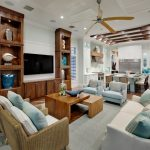 Kitchen Family Room Wooden Shelves Ceiling Fan Wooden Coffee Table White Sofa Blue Chairs Blue Pillows Gray Rug Windows White Cabinets Range Hood Stovetop