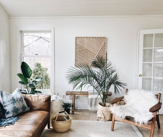 living room, wooden floor, grey rug, white wall, brown elather, wooden chair, wooden bench, plant, window