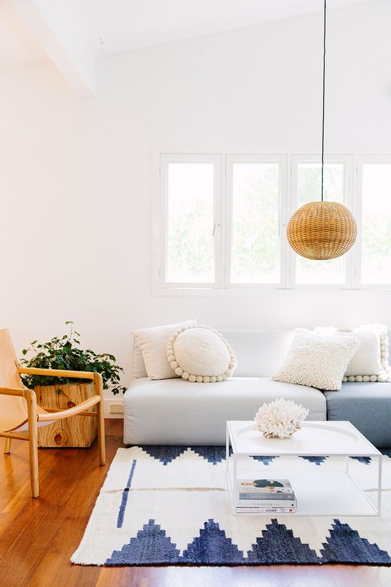 living room, wooden floor, wooden chair, white blue sofa, white blue rug, rattan pendant