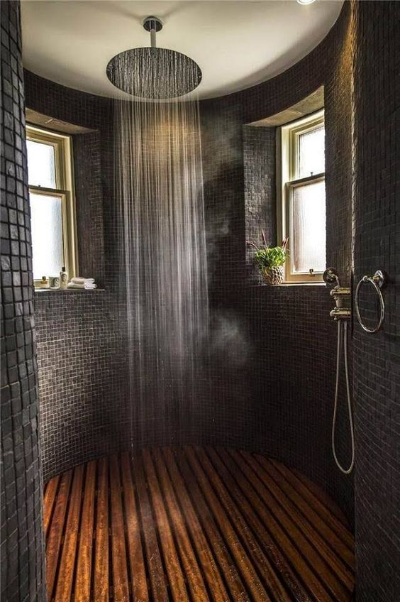 rond bathroom, wooden floor, black tiny square wall tiles, vertical shower