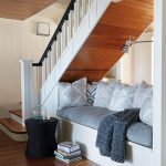 Seats Under The Stairs, White Built In Bench, White Stairs, Brown Wooden Floor, Grey Cushion, Grey Pillows, Silver Sconce