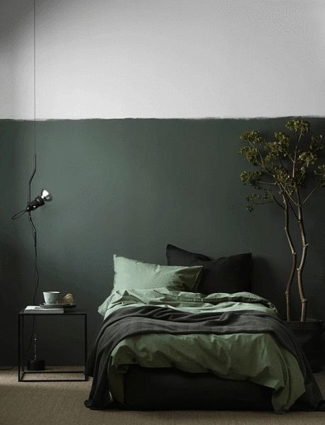 simple industrial floor lamp, green white wall, dark green bed, brown rug