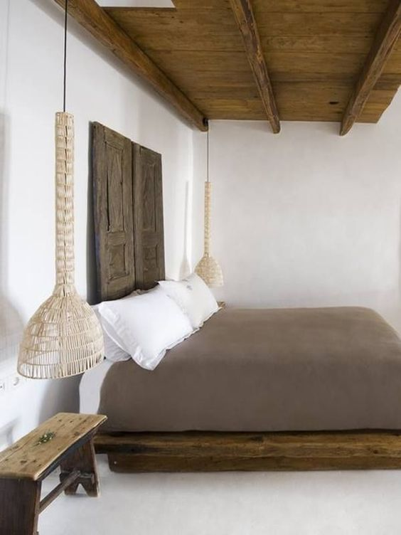 wooden platform, white bed, grey linen, white wall, wooden ceiling, wooden bench, white floor