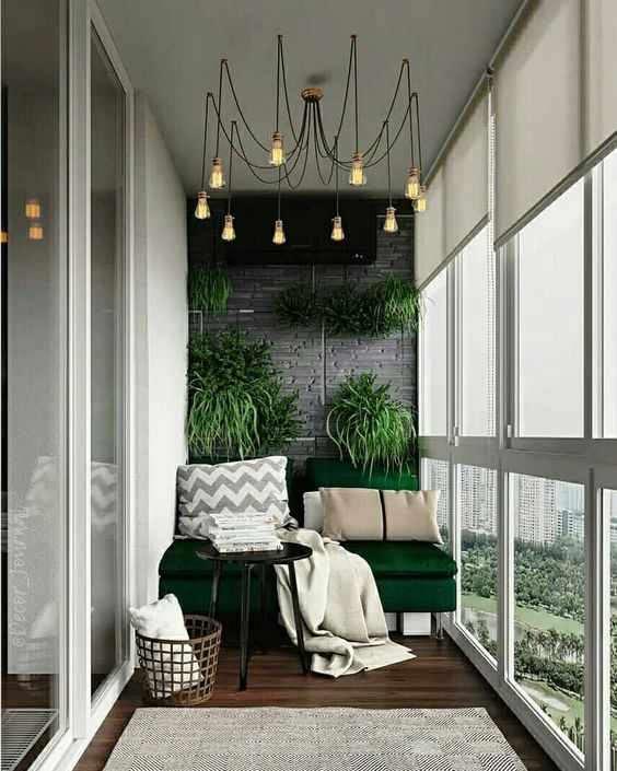 balcony, dark wooden floor, green sofa, white wall, grey exposed accent wall, orange small pendants, grey rug