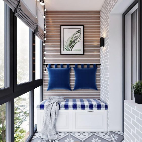 balcony, patterned floor tiles, exposed tiles, striped wall, white bench, checkered cushion, blue pillows