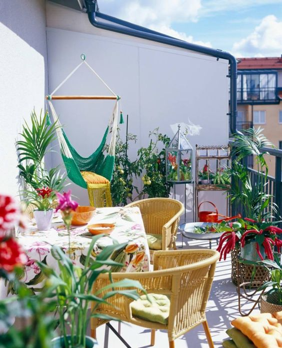 balcony, white floor, white wall, green swing, rattan chairs, table with colorful clothe, plants, rattan pots, pillows