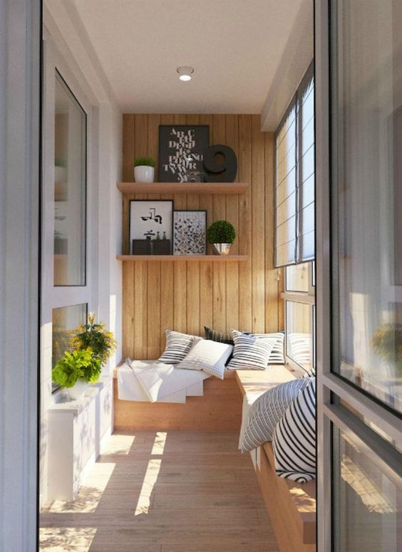 balcony, wooden floor, wooden built in bench, wooden accent wall, white wall, curtain, floating shelves, pillows