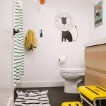 Bathroom, Black Tiny Hexagonal Tiles, White Wall, White Toilet, Wooden Cabinet, White Top, Striped Curtain, Yellow Stairs