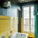 Bathroom, Black Wall, Yellow Square Tiles On The Wall And Tub, Dark Flowery Ceiling, Black Floor, Green Curtain
