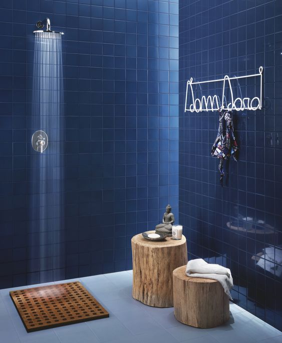 bathroom, blue floor, dark blue wall tiles, wooden stoo, shower,