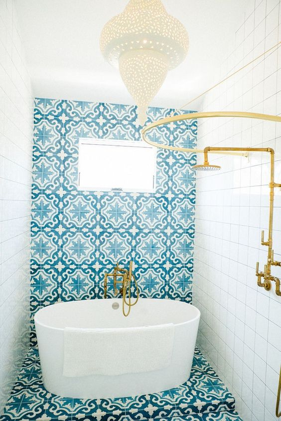 bathroom, blue patterned accent wall and floor, white wall tiles, moroccan pendant, golden shower