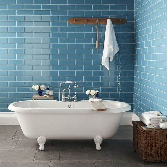 bathroom, blue subway wall tiles, grey floor, white tub, rattan basket