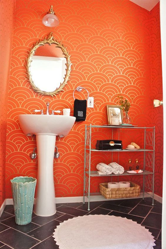 bathroom, gray floor tiles, orange wave patterned wall, white sink, shelves, golden frame mirror