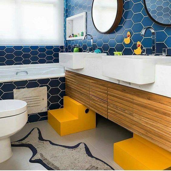 bathroom, grey floor, blue hexagonal wall tiles, wooden cabinet, yellow stairs, white sink, round mirror