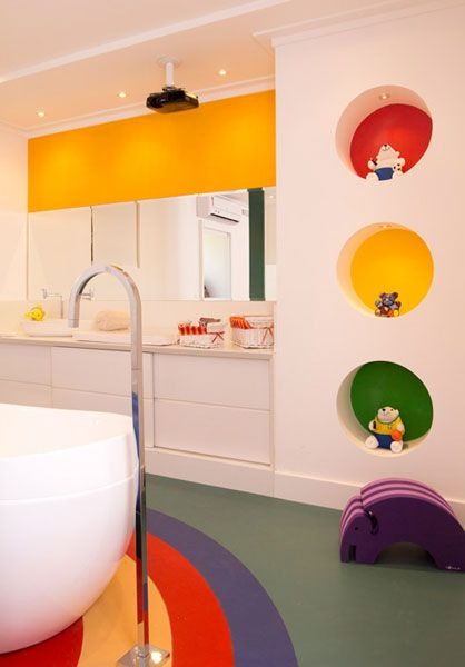 bathroom, grey floor, colorful rug, white round rug, white wall, round hole, yellow line on top of the mirror, white cabinet