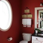 Bathroom, Grey Floor, Red Wal, Wite Framed Round Window, White Cabinet, White Framed Mirror, White Sconce, White Toilet