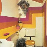 Bathroom, Grey Tiny Floor Tiles, Yellow Walls With Yellow Purple Lines, Yellow Floating Shelves, White Toilet