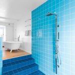 Bathroom, Light Blue Wall Tiles, Dark Blue Floor Tiles, White Wall, Wooden Floor In Tub Area
