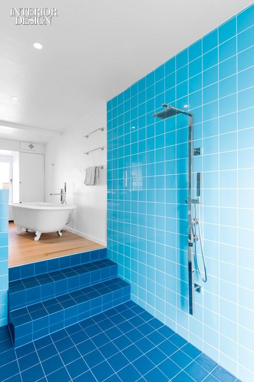 bathroom, light blue wall tiles, dark blue floor tiles, white wall, wooden floor in tub area