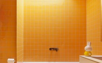 bathroom, marble floor tiles, yellow wall tiles, white tub, pale yellow floating vanity, white toilet