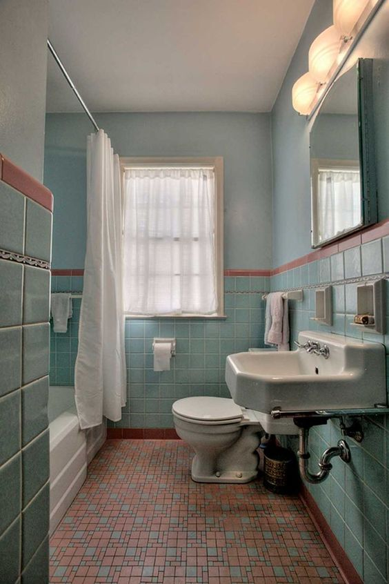 bathroom, orange patterned floor tiles, light teal wall tiles and wall, white toilet, white sink, white tub, white curtain