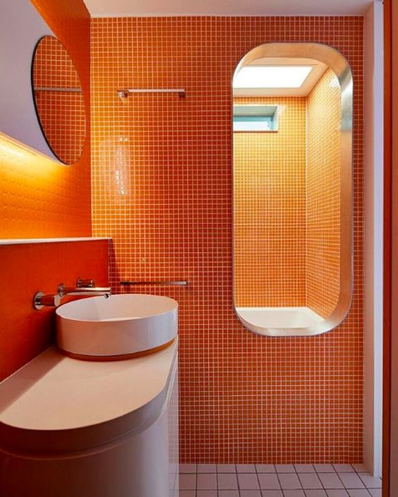bathroom, white floor tiles, orange wall square tiles, white modern vanity, white round sink, mirror