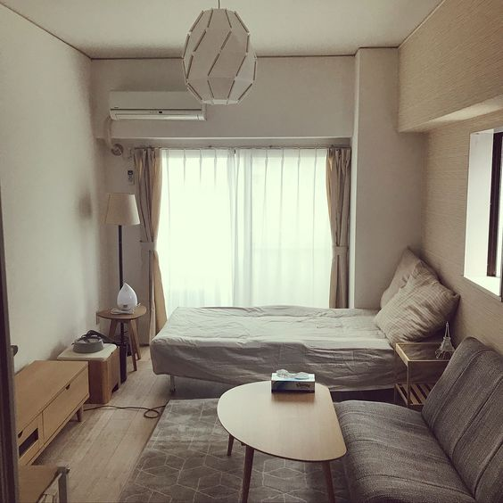 bedroom, white wall, grey foldable sofa, wooden coffee table, wooden low cabinet, wooden side table, grey rug