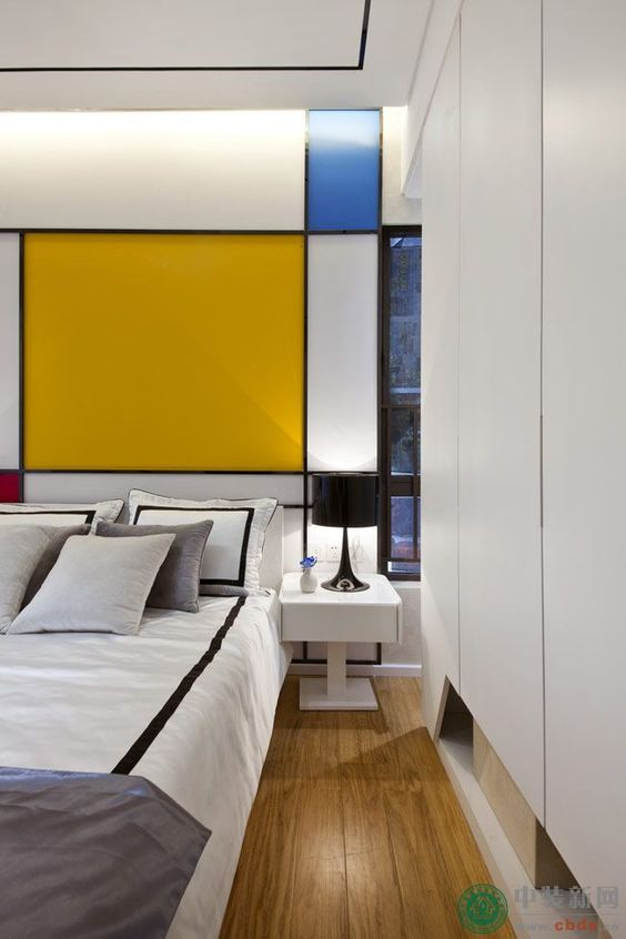 bedroom, wooden floor, white cupboard, white bedding, colorful blocks pop art on the wall, white side table, black table lamp