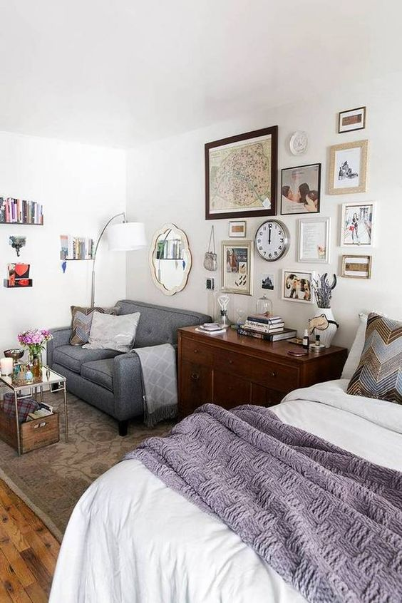 bedroom, wooden floor, white wall, white bedding, wooden cabinet, grey sofa, white floor lamp, grey rug